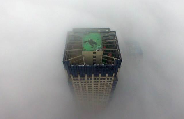 ตึกสูงระฟ้าในเมืองหยังโจว มณฑลเจียงซู ถูกห่อหุ้มด้วยหมอกหนาเมื่อวันที่ 2 ม.ค. 2017 หมอกหนาในเมืองทำให้ทัศนะวิสัยการมองเห็นลดลง บางช่วงไม่ถึง 50 เมตร (ภาพ เอเอฟพี)