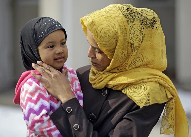 <i>นิโม ฮาชี ผู้ลี้ภัยชาวโซมาเลีย อุ้ม ตัสลิม ลูกสาวของเธอ ที่บริเวณบ้านของพวกเขาเมื่อวันอังคาร (31 ม.ค.)  ฮาชิซื้อโต๊ะและเก้าอี้นวมตัวใหม่เข้าอพาร์ตเมนของเธอในเมืองซอลต์เลกซิตี้  ด้วยความคาดหวังว่าเมื่อวันศุกร์ (27 ม.ค.) จะได้รวมครอบครัวอยู่กับสามีของเธอครบหน้าครบตาเป็นครั้งแรกในรอบ 3 ปี  ทว่าเขายังมาไม่ถึงบ้านและยังไม่มีโอกาสเห็นหน้าบุตรสาววัย 2 ขวบซึ่งเขาไม่เคยเจอเลย  เนื่องจากเขาเป็นหนึ่งในผู้คนหลายร้อยที่เจอพิษคำสั่งฝ่ายบริหารของประธานาธิบดีทรัมป์ ซึ่งห้ามผู้ลี้ภัยและนักเดินทางจาก 7 ประเทศมุสลิม โดย 1 ในนั้นได้แก่โซมาเลีย </i>
