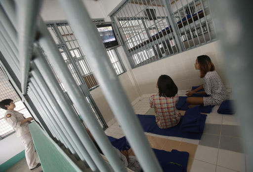 In this Jan. 6, 2017 photo, a female officer locks a cell as transgender inmates watch TV at Pattaya Remand Prison in in Pattaya, Chonburi province, Thailand. The prison separates lesbian, gay, bisexual and transgender prisoners from other inmates, a little-known policy despite being in place nationwide since 1993, according to the Department of Corrections. (AP Photo/Sakchai Lalit)