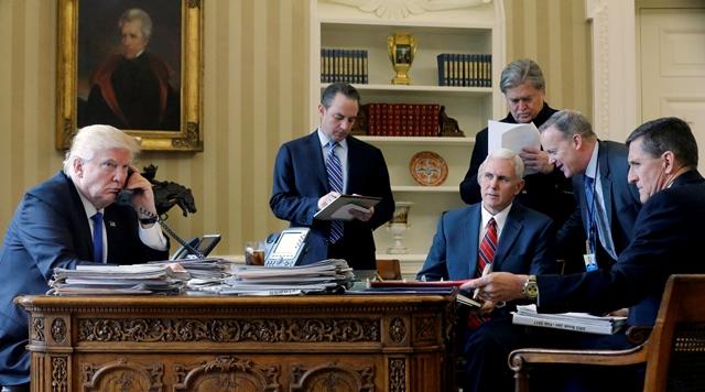 <i>ภาพจากแฟ้มถ่ายเมื่อวันที่ 28 มกราคม 2017 ขณะที่ประธานาธิบดีโดนัลด์ ทรัมป์ ของสหรัฐฯ (ซ้าย) พูดคุยโทรศัพท์กับประธานาธิบดีวลาดิมีร์ ปูตินของรัสเซีย  โดยที่ ไมเคิล ฟลินน์ ที่ปรึกษาฝ่ายความมั่นคงแห่งชาติ (ขวาสุด) ก็ได้รับความไว้วางใจให้อยู่ในห้องด้วย </i>