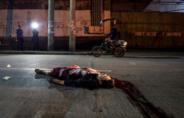 <i>ภาพถ่ายเมื่อวันศุกร์ (17 ก.พ.) ที่ผ่านมา แสดงให้เห็นศพชายผู้หนึ่งที่ถูกสังหารโดยมือปืนซึ่งไม่ทราบว่าเป็นใคร  นอนอยู่บนถนนในกรุงมะนิลา, ฟิลิปปินส์   ทั้งนี้หลังการประกาศสงครามปราบยาเสพติดของประธานาธิบดีโรดริโก ดูเตอร์เต ได้มีผู้เสียชีวิตลักษณะเช่นนี้เป็นเรือนพัน </i>