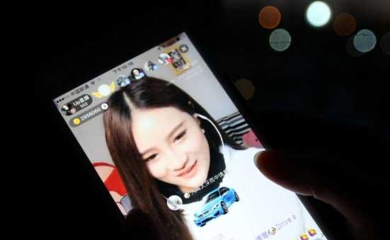 ไห่ เจินเจิน ใช้แอพพลิเคชั่น UpLive ในโทรศัพท์สมาร์ทโฟน ถ่ายทอดสดกิจกรรมทั่วไปในแต่ละวันของตน ไม่ว่าจะเป็นการทำงานบ้าน ล้างจาน ร้องเพลง หรือแค่การพูดคุยกับผู้คนเพียงวันละสองชั่วโมง ในทุกวันทำงานธรรมดาของเธอ (ภาพเซาท์ไชน่ามอร์นิงโพสต์)