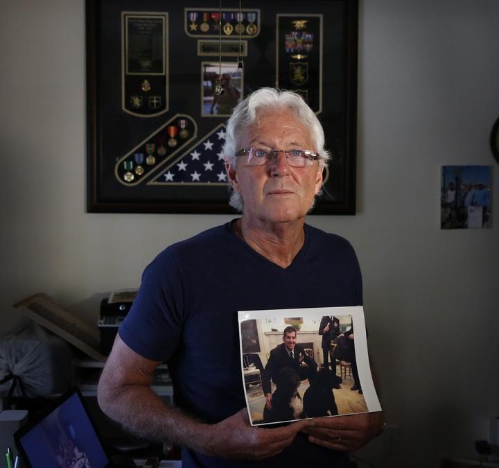 """ภาพของไมอามี่ เฮรัลด์ ถ่ายในเดือนกุมภาพันธ์ 2017 นี้ แสดงให้เห็น วิลเลียม โอเวนส์ ถือภาพของ """"ไรอัน"""" บุตรชายคนเล็กสุดของเขาที่เป็นสมาชิกหน่วยซีลด์แห่งกองทัพเรือสหรัฐฯ  ผู้เสียชีวิตไปในการปฏิบัติการจู่โจมในเยเมน"""