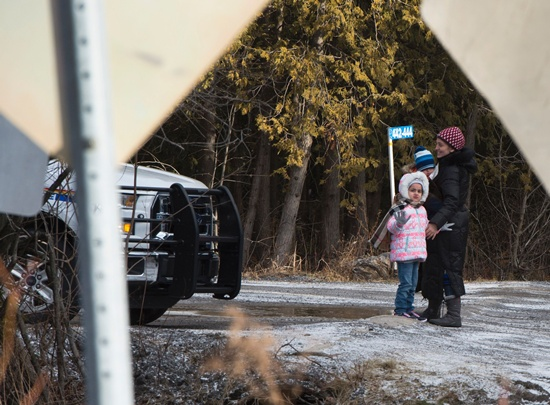 Champlain, United States: The family of Erkan Cuce, from Turkey, wave goodbye to family members who dropped them off at the US/Canada border February 26, 2017, in Champlain, NY. The family was arrested by the RCMP after crossing. Canadas Prime Minister Justin Trudeau is facing growing political pressure to address the steady stream of asylum seekers who have been braving freezing temperatures to cross into Canada from the US by foot. AFP/Don Emmert