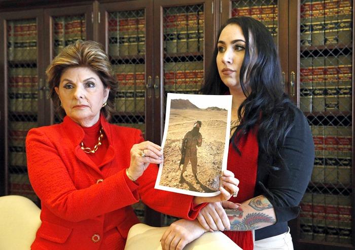 <i>อดีตนาวิกโยธินอเมริกัน อีริกา บุตเนอร์ (ขวา) และทนายความ กลอเรีย ออลเรด  ช่วยกันถือภาพบุตเนอร์ขณะอยู่ในเครื่องแบบ  บุตเนอร์เป็นทหารหญิงผู้หนึ่งที่ออกมาแสดงตัวร้องเรียนว่าตกเป็นเหยื่อถูกโพสต์ภาพลับทางออนไลน์โดยที่พวกเธอไม่ได้ยินยอม </i>