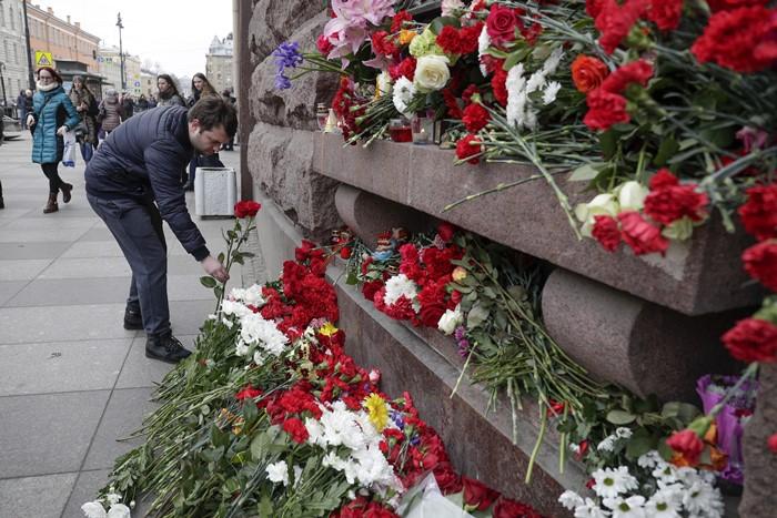 "<i>ชายผู้หนึ่งวางช่อดอกไม้ ณ สถานไว้อาลัยชั่วคราว ที่บริเวณด้านหน้าของสถานีรถไฟใต้ดิน ""สถาบันเทคโนโลยี"" (Tekhnologicheskiy institut) ในเมืองเซนต์ปีเตอร์สเบิร์ก, รัสเซีย เมื่อวันอังคาร (4 เม.ย.) </i>"
