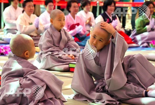 A child reacts after having his head shaved by Buddhist monks during a ceremony entitled Children Becoming Buddhist Monks, at the Jogye temple in Seoul on April 19, 2017. Following the ceremony the children stay at the temple where they are taught about Buddhism for two weeks ahead of celebrations for Buddhas birthday on May 3 this year. Jung Yeon-Je/AFP