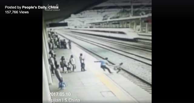 เจ้าหน้าที่สถานีรถไฟ พุ่งเข้าขวางนักศึกษาหญิงคนหนึ่ง ที่พยายามฆ่าตัวตายด้วยการวิ่งตัดหน้ารถไฟความเร็วสูง (ภาพจากคลิปฯ)