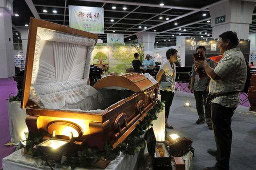 Visitors look at a paper casket at the Asia Funeral and Cemetery Expo & Conference in Hong Kong, Thursday, May 18, 2017. The expo underscores how for some investors, Asias rapidly aging population makes its death industry a potentially lucrative market. Asias aging population is projected to hit 923 million by mid-century, according to an Asian Development Bank, putting the region on track to become the oldest in the world. (AP Photo/Vincent Yu)