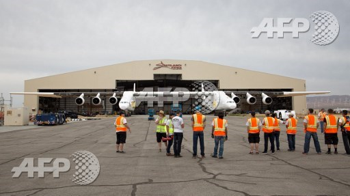 Crew members look on as the Stratolaunch plane is pushed out of the hanger for the first time in the Mojave desert, California on May 31, 2017. April Keller/Stratolaunch Systems Corp/AFP