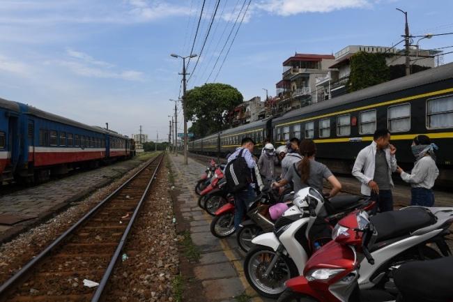 <br><FONT color=#000033>ชาวเวียดนามยืนอยู่ใกล้กับรางรถไฟที่สถานีรถไฟแห่งหนึ่งในกรุงฮานอย ระหว่างปี 2553 ถึงปี 2558 การเดินทางทางอากาศในเวียดนามมีผู้ใช้บริการเพิ่มขึ้นถึง 2 เท่า ที่จำนวนมากกว่า 31 ล้านคน ขณะที่จำนวนผู้ใช้บริการรถไฟยังคงทรงตัวที่ 11 ล้านคนเท่านั้น. -- Agence France-Presse/Hoang Dinh Nam.</font></b>