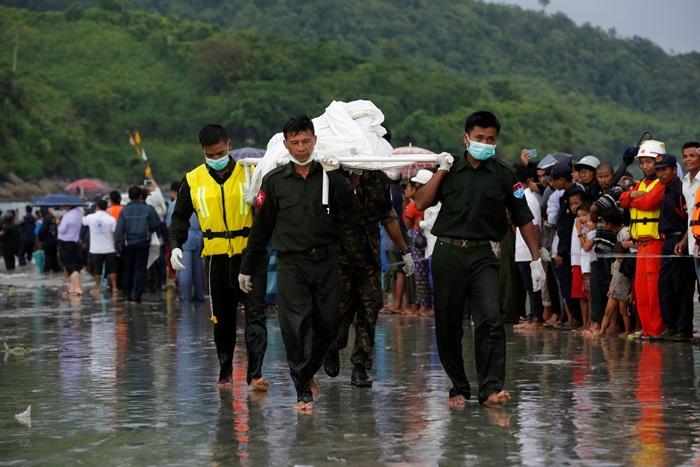 <I>ทหารพม่าช่วยกันลำเลียงศพผู้เสียชีวิตจากเครื่องบินขนส่งทหารตกลงกลางทะเลอันดามัน ขึ้นมาจากเรือซึ่งบรรทุกร่างผู้เสียชีวิตมายังบริเวณชายหาดนอกเมืองลองโลง ทางภาคใต้ของประเทศเมื่อวันพฤหัสบดี (8 มิ.ย.) </I>