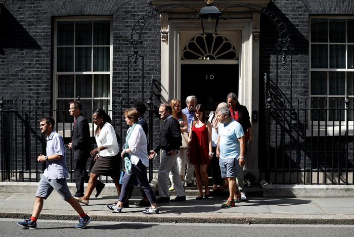 <i>เหยื่อในกรณีไฟไหม้อาคารเกรนเฟลล์ ทาวเวอร์ และพวกอาสาสมัคร เดินออกมาจากทำเนียบนายกรัฐมนตรีอังกฤษ บ้านเลขที่ 10 ถนนดาวนิ่ง ในกรุงลอนดอน เมื่อวันเสาร์ (17 มิ.ย.) ภายหลังพบปะกับนายกรัฐมนตรีเทเรซา เมย์  </i>