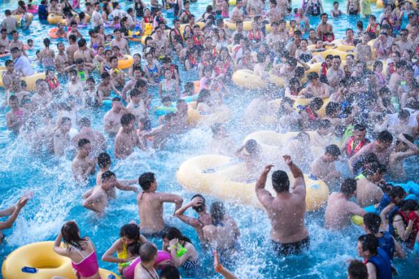 """ชมภาพชาวจีนแห่เล่นน้ำดับร้อนฤดูคิมหันต์ ก่อปรากฎการณ์ """"ทะเลมนุษย์"""" ในสวนน้ำ"""