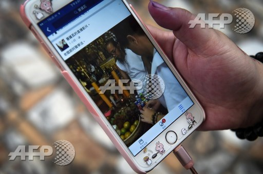 This photograph taken on May 20, 2017 shows a video on the mobile phone of Taiwanese client Ann Lui of Thai hermit Toon performing a ritual in the northern Thai province of Khon Kaen. Lillian Suwanrumpha/AFP