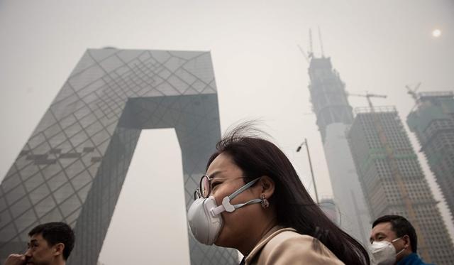 หญิงชาวจีนสวมหน้ากากกรองฝุ่นพิษในวันที่กรุงปักกิ่งเผชิญอากาศย่ำแย่ (ภาพ เอเอฟพี)