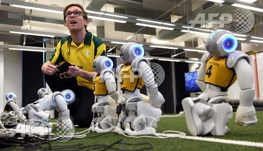 Jeremy Collette prepares soccer robots in Sydney on July 21, 2017, as Australia's five-time world champions of robot soccer, the University of New South Wales (UNSW) Runswift team, heads to Japan this weekend to try and recapture the international trophy for a record sixth time, facing off against powerful teams from Germany and the USA. William West/AFP