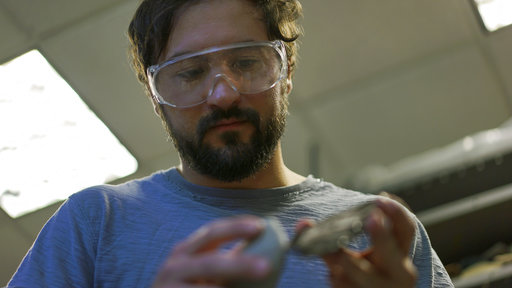 In this June 1, 2017, photo, Metin Eren, an archaeologist at Kent State University, looks at a newly chipped flake of obsidian in Kent, Ohio. (AP Photo/Dake Kang)