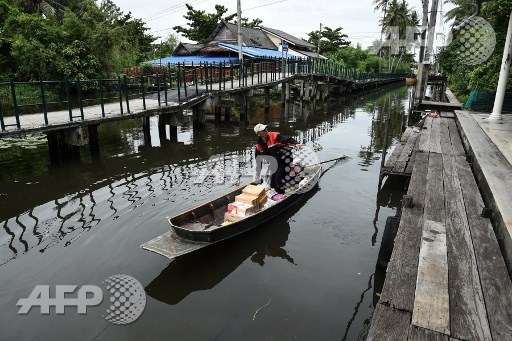 This photo taken on July 17, 2017 shows postman Nopadol Choihirun loading parcels and mail into his boat on the canal in the Bang Khun Thian district on the outskirts of Bangkok. Nopadol Choihirun is one of Bangkoks last remaining postmen to deliver mail by boat to waterfront homes in low-lying parts of the capital. Lillian Suwanrumpha/AFP