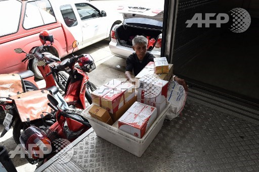 This photo taken on July 17, 2017 shows postman Nopadol Choihirun handling parcels and mail from the Bang Khun Thian post office on the outskirts of Bangkok. Nopadol Choihirun is one of Bangkoks last remaining postmen to deliver mail by boat to waterfront homes in low-lying parts of the capital. Lillian Suwanrumpha/AFP
