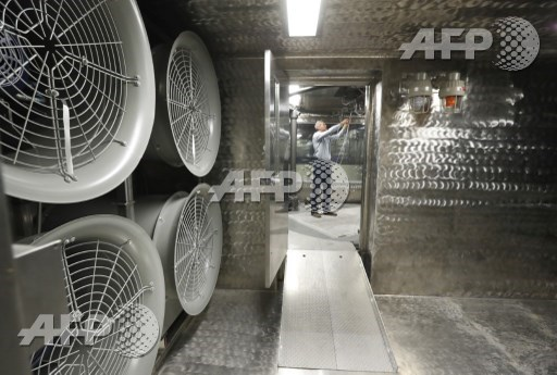 DUGWAY, UT: Large fans hang on a wall as chief of the Chemical Test Branch Adam Rogers checks out a wiring harness in a wind tunnel testing room at the small item decontamination testing chamber facility at the U.S. Armys Dugway Proving Ground on August 15, 2017 in Dugway, Utah. George Frey/Getty Images/AFP