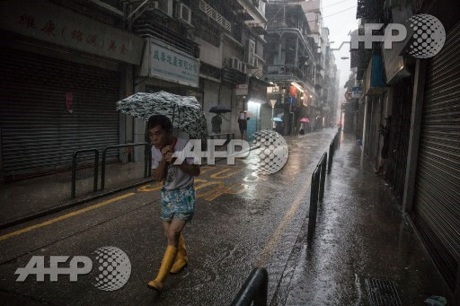 A man uses an umbrella during heavy rain as severe tropical storm Pakhar passes over Macau on August 27, 2017. A powerful storm lashed Hong Kong and Macau early on August 27, just days after a punishing typhoon swept through southern China and claimed at least 18 lives. Dale de la Rey/AFP