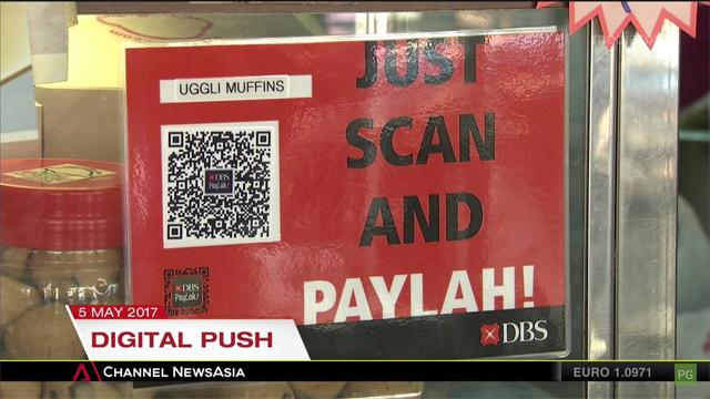 ภาพจาก Channel News Asia - ธนาคารดีบีเอสให้บริการสแกนคิวอาร์โค้ดตามร้านค้าเพื่อชำระเงินผ่านแอปพลิเคชัน DBS PayLah! ขณะที่ทางการสิงคโปร์เตรียมผลักดันระบบคิวอาร์โค้ดเพื่อชำระเงินตามร้านค้าในอีก 6 เดือนข้างหน้า