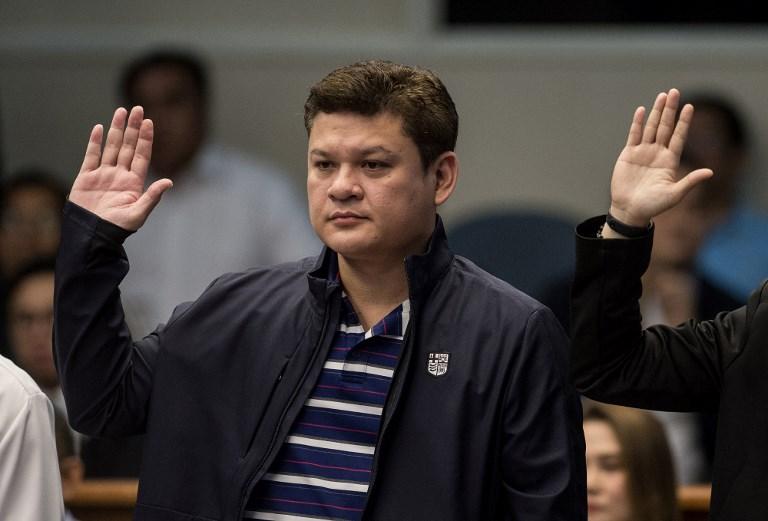 เปาโล ดูเตอร์เต รองนายกเทศมนตรีเมืองดาเวาและบุตรชายของประธานาธิบดี โรดริโก ดูเตอร์เต ยกมือให้คำสัตย์ต่อวุฒิสภา ขณะเข้ารับการไต่สวนข้อหาพัวพันแก๊งค้ายาเสพติด เมื่อวันที่ 7 ก.ย.