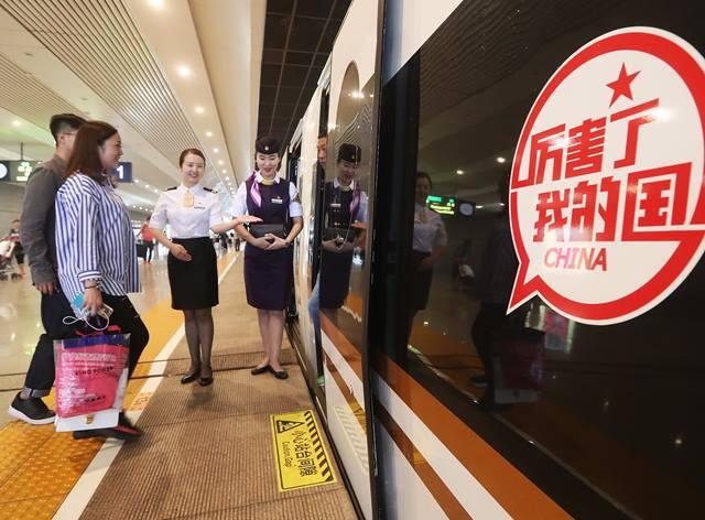 """ผู้โดยสารกำลังขึ้นรถไฟหัวกระสุน """"ฟู่ซิง""""  ที่สถานีรถไฟหงเฉียว นครเซี่ยงไฮ้ เมื่อวันที่ 21 ก.ย. ซึ่งเป็นเที่ยวประเดิมของจ้าวความเร็วปานจรวด 350 กม./ชม. ป้ายข้อความที่ขบวนรถไฟแปลว่า """"ประเทศจีนของเรา ยอดเยี่ยม!"""" (ภาพ ซินหวา)"""