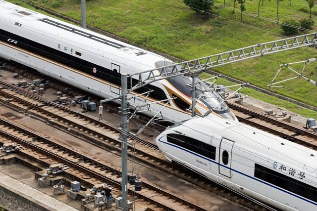 """รถไฟหัวกระสุนฟู่ซิง (ซ้าย) กำลังแล่นผ่านนครหนันจิงในอัตราเร็ว 350 กม./ชม. ส่วนขบวนรถไฟความเร็วสูง (ขวา) เป็นขบวน """"เหอเสีย"""" วิ่งในอัตราเร็ว 300 กม,/ชม.ภาพเมื่อวันที่ 21 ก.ย. (ภาพ ซินหวา)"""
