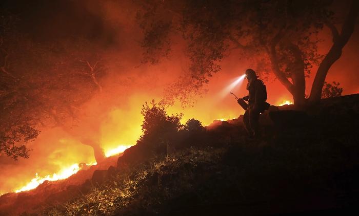 <i>เจ้าหน้าที่ผจญเพลิงของแผนกควบคุมไฟป่าแคลิฟอร์เนีย เฝ้าติดตามพระเพลิงที่โหมฮือตรงด้านหน้าของไฟป่า ณ บริเวณนอกถนนไฮโรด เหนือหุบเขาโซโนมา เมื่อวันพุธ (11 ต.ค.) </i>