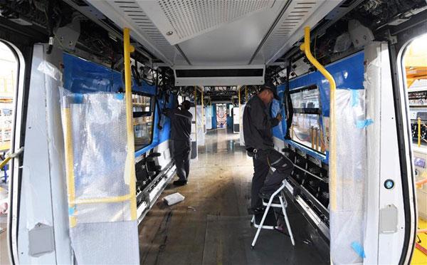 เจ้าหน้าที่ติดตั้งระบบไฟฟ้าของรถไฟที่โรงงานกิจการรถไฟฉางชุน [ภาพซินหวา]
