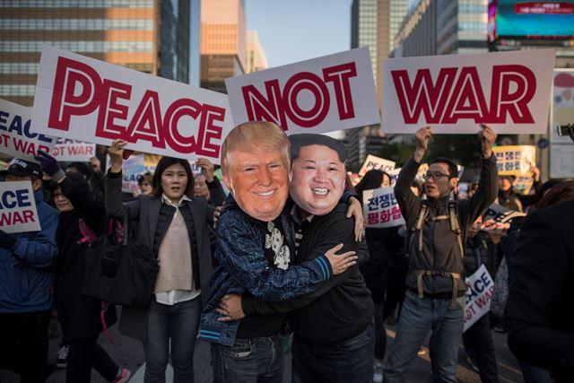 ผู้ชุมนุมที่แต่งเป็นผู้นำเกาหลีเหนือ คิม จองอึน (ขวา) และประธานาธิบดีโดนัลด์ ทรัมป์ ของสหรัฐฯ (ซ้าย) สวมกอดกันในระหว่างการชุมนุมอย่างสันติในโซลเมื่อวันที่ 5 พฤศจิกายน ปี 2017