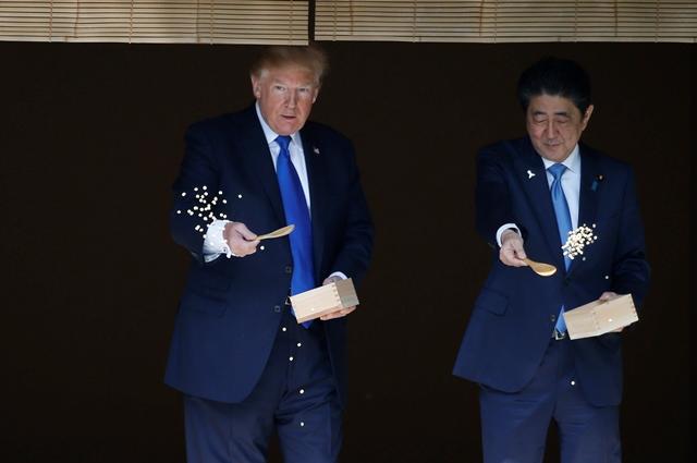ประธานาธิบดีโดนัลด์ ทรัมป์ ของสหรัฐฯ (ซ้าย) และนายกรัฐมนตรี ชินโซ อาเบะ ของญี่ปุ่น (ขวา) ให้อาหารปลาคาร์ฟในระหว่างพิธีต้อนรับในโตเกียว เมื่อวันที่ 6 พฤศจิกายน ปี 2017