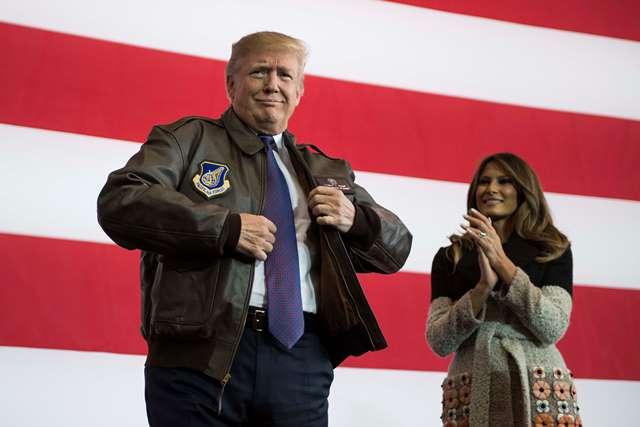 ประธานาธิบดีโดนัลด์ ทรัมป์ ของสหรัฐฯ (ขวา) เตรียมปราศรัยต่อทหารสหรัฐฯ ในขณะที่ เมลาเนีย ภรรยาของเขายืนมองในระหว่างการเยือนฐานทัพอากาศโยโกโตะของสหรัฐฯ เมื่อวันที่ 5 พฤศจิกายน ปี 2017