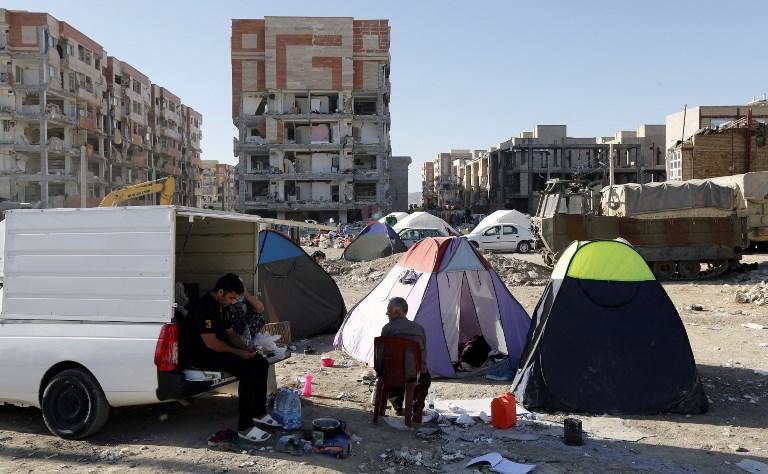 <i>ชาวอิหร่านส่วนหนึ่งกางเต็นท์เพื่อใช้เป็นที่พักชั่วคราว บริเวณใกล้ๆ กับอาคารที่ได้รับความเสียหายหนักจากแผ่นดินไหว ในเมืองซาร์โปล-อี ซาฮับ ทางภาคตะวันตกของประเทศ เมื่อวันอังคาร (14 พ.ย.) </i>