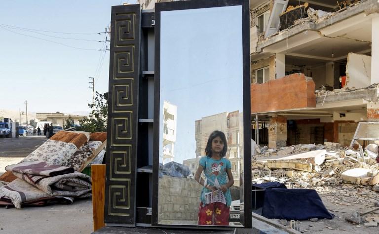 <i>เด็กหญิงชาวอิหร่านมองผ่านกระจกซึ่งถูกขนย้ายออกมาจากอาคารที่ได้รับความเสียหายเพราะแผ่นดินไหว ในเมืองซาร์โปล-อี ซาฮับ </i>