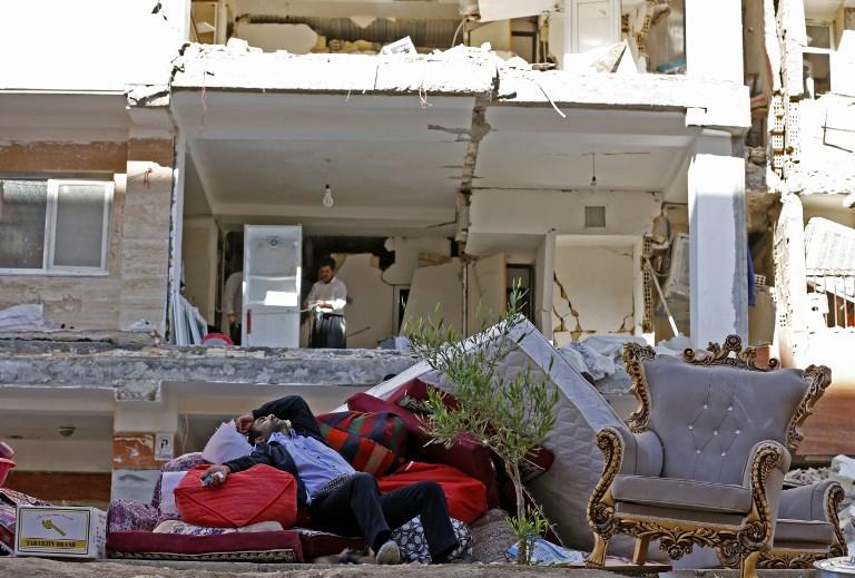 <i>ชายชาวอิหร่านพักผ่อนเหนือข้าวของซึ่งขนย้ายออกมาจากอาคารที่ได้รับความเสียหายจากแผ่นดินไหว ในเมืองซาร์โปล-อี ซาฮับ </i>
