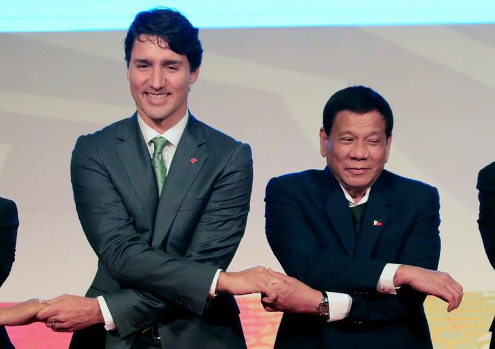 จัสติน ทรูโด นายกรัฐมนตรีแคนาดา(ซ้าย) ไขว้แขนจับมือกับ โรดริโก ดูเตอร์เต ประธานาธิบดีฟิลิปปินส์(ขวา) ถ่ายภาพหมู่ระหว่างการประชุมสุดยอดผู้นำอาเซียน-แคนาดา ครั้งที่ 40 ในกรุงมะนิลา ประเทศฟิลิปปินส์ เมื่อวันอังคาร(14พ.ย.)