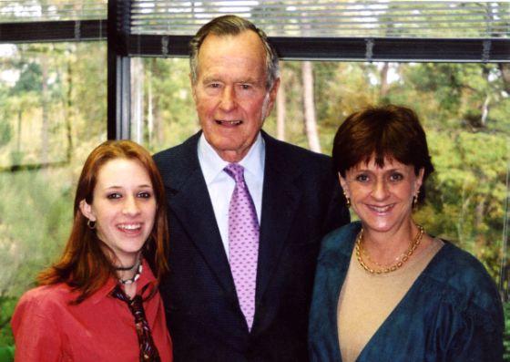 ภาพจากครอบครัวคอร์ริแกน เป็นภาพที่ โรสลิน คอร์ริแกน(ซ้ายสุด) และ ซารี ยัง (ขวาสุด) แม่ของเธอ กำลังถ่ายรูปร่วมกับอดีตประธานาธิบดีสหรัฐฯ จอร์จ เฮอร์เบิร์ต บุช  ท่ามกลางคำกล่าวหาว่าเขาใช้โอกาสนี้จับก้นของคอร์ริแกน