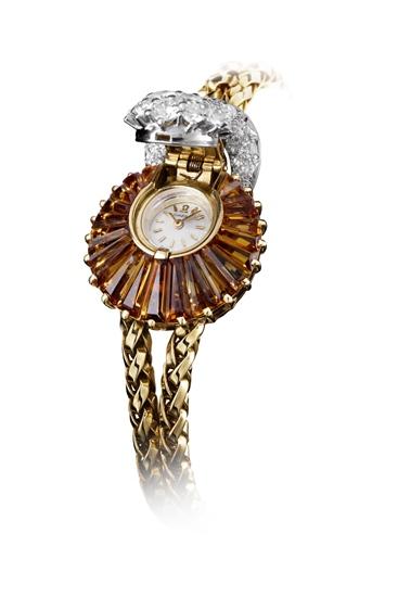 Topaz Jewelry Secret Watch สร้างสรรค์ขึ้นโดย Jean Hauck of Geneva ตกแต่งด้วยบุษราคัมสีส้มตัดเป็นรูปสามเหลี่ยมขนาดเล็ก 21 เม็ด เรียงเป็นรูปพัดอยู่ล้อมรอบตัวเรือน และประดับเพชรน้ำงาม 31 เม็ดที่ฝาครอบหน้าปัดและห่วง