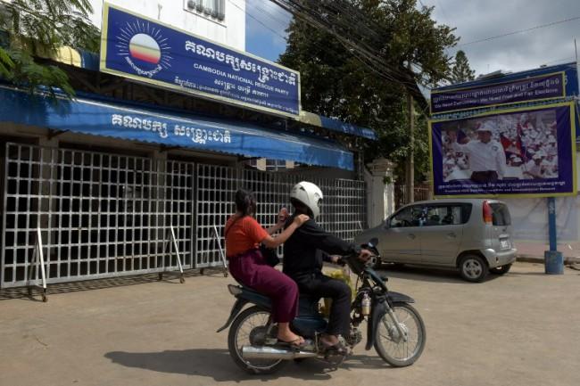 ชาวเขมรขี่รถจักรยานยนต์ผ่านสำนักงานพรรคกู้ชาติกัมพูชาในกรุงพนมเปญ โดยพรรคกู้ชาติกัมพูชาถูกศาลสูงตัดสินยุบพรรคตามคำร้องของรัฐบาลเมื่อสัปดาห์ก่อน. -- Agence France-Presse/Tang Chhin Sothy.