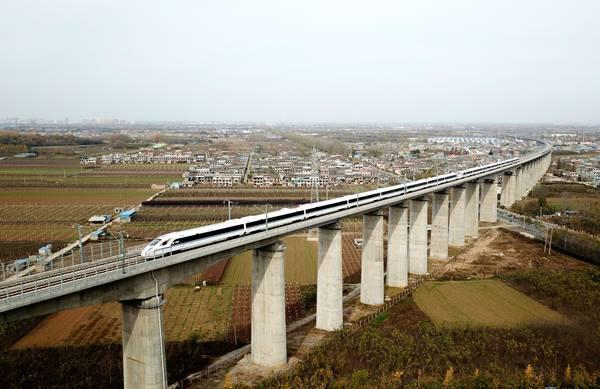จ้าวความเร็วรถไฟหัวกระสุนวิ่งข้ามสะพานระหว่างการทดลองเดินรถบนเส้นทางรถไฟความเร็วสูงเชื่อมซีอัน มณฑลส่านซี และเฉิงตู มณฑลเสฉวน เมื่อวันที่ 22 พ.ย. (ภาพ ซินหวา)