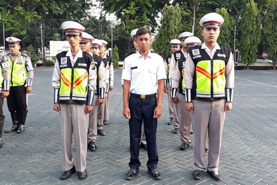 Polisi (C in white) attends a police roll call in Pasuruan on November 21, 2017. An Indonesian can thank his parents after his unusual name not only spared him a traffic ticket but also landed him a job with the police who stopped him. AFP