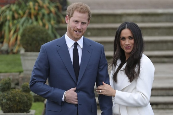 Britains Prince Harry stands with his fiancee US actress Meghan Markle as she shows off her engagement ring whilst they pose for a photograph in the Sunken Garden at Kensington Palace in west London on November 27, 2017, following the announcement of their engagement. Britains Prince Harry will marry his US actress girlfriend Meghan Markle early next year after the couple became engaged earlier this month, Clarence House announced on Monday. Daniel Leal-Olivas/AFP