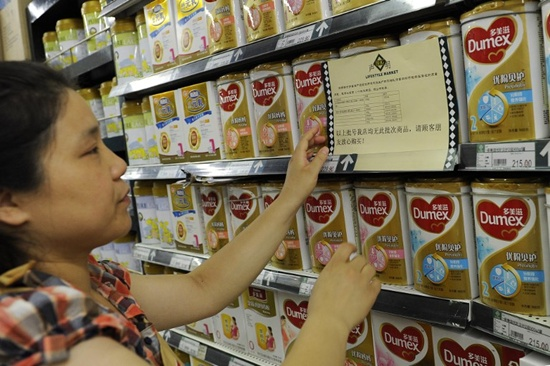 (FILES) This file photo taken on August 5, 2013 shows a woman checking a guarantee announcement on a shelf of baby formula, which uses the New Zealand dairy company Fonterra as its raw material supplier, at a supermarket in Hefei, northern Chinas Anhui province. New Zealand dairy giant Fonterra was ordered to pay French rival Danone 125 million USD in damages on December 1, 2017 over a baby formula botulism scare. The huge payout came after Danone sued over the 2013 issue, when fears about contamination in Fonterra-supplied ingredients forced global formula recalls, including Danone brands. AFP