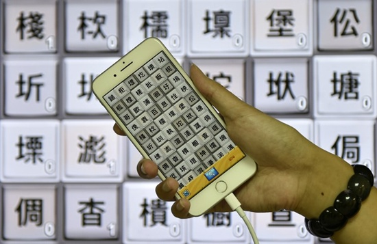 This picture taken on November 2, 2017 shows Steve Tsai, an APP designer of Zihun, displaying his smart phone showing traditional Chinese characters during an interview in Taipei. Sam Yeh/AFP