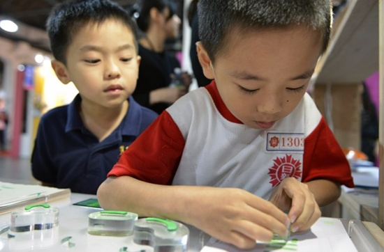 This picture taken on October 20, 2017 shows a boy stamping a Chinese character during an exhibition in Taipei. Sam Yeh/AFP