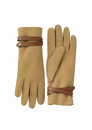 ถุงมือหนังลูกแกะ ในเฉดสีอำพันมาพร้อมสายรัดข้อมือเพื่อเพิ่มความแน่นหนาในการสวมใส่