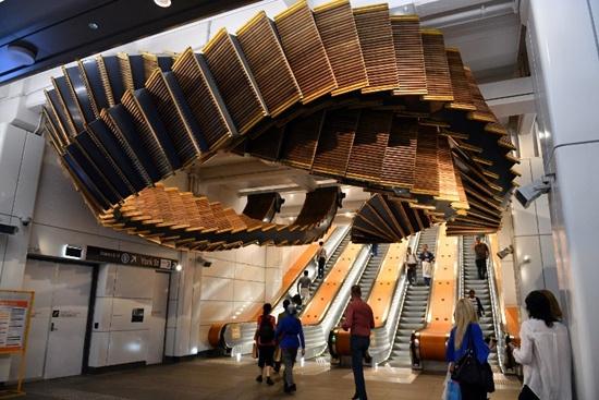 People walk under the sculpture Interloop, made from old wooden escalators in Wynyard railway station, by artist Chris Fox in Sydney on December 7, 2017. Saeed Khan/AFP
